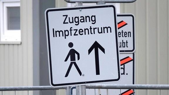 Ein Schild weist auf den Zugang zu einem Corona-Impfzentrum hin