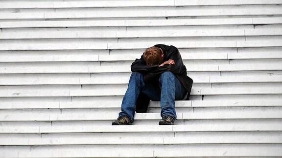 Ein Mann sitzt deprimiert auf einer Treppe.