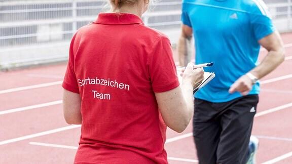 Abnahme des Deutschen Sportabzeichen auf einem Sportplatz.