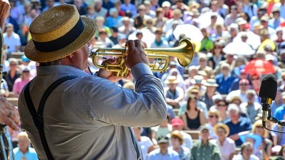 Ein Trompeter spielt vor zahlreichen Zuschauern.