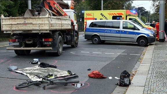 In Dresden ist ein Radfahrer bei einem Unfall ums Leben gekommen. Auf der Straße liegt das zerbeulte Fahrrad.