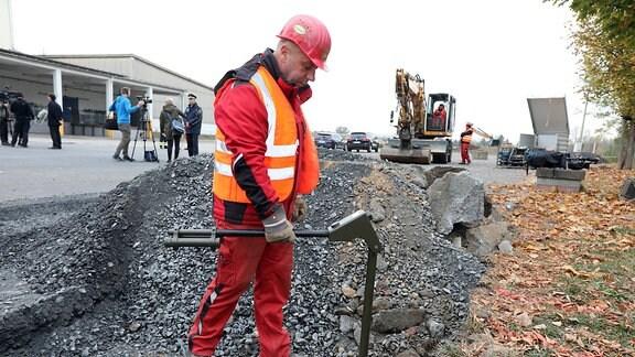 Ein Mann untersucht den Boden auf eine Bombe