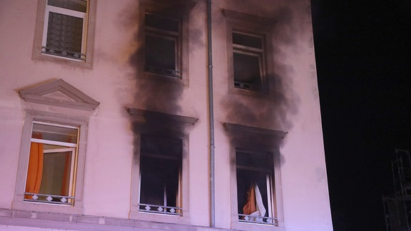 Schwarzer Rauch dringt aus zwei Fenstern.
