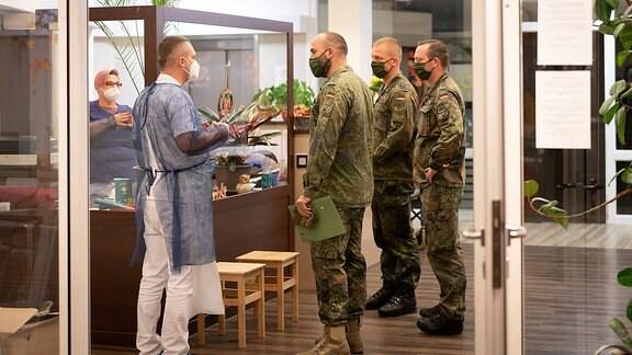 Drei Soldaten im Gespräch mit Mitarbeitern eines Pflegeheims