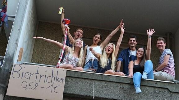 Siebern Personen sitzen auf einem Balkon