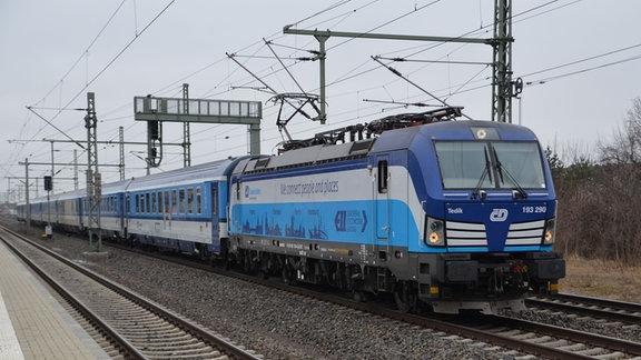 Ein Eurocity-Zug fährt an einem trüben Tag durch Dresden.