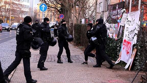 Polizisten halten eine Hausbesetzerin fest