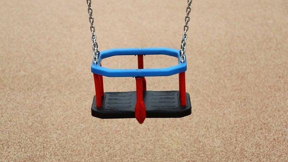 Leere Kinderschaukel auf einem Spielplatz