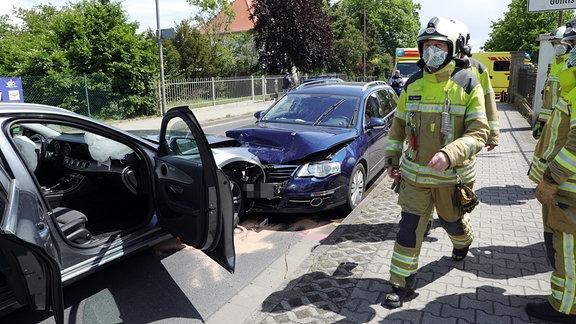 Ein blaues Auto ist auf der falschen Straßenseite frontal in ein silbernes Auto gefahren. Die Fahrer- und Beifahrertüren stehen offen. Feuerwehrleute laufen umher und versuchen ausgelaufenen Treibstoff zu binden und zu beseitigen. De Unfall passierte am 24.05.2020, mittags gegen 12:30 Uhr in Dresden-Gohlis.