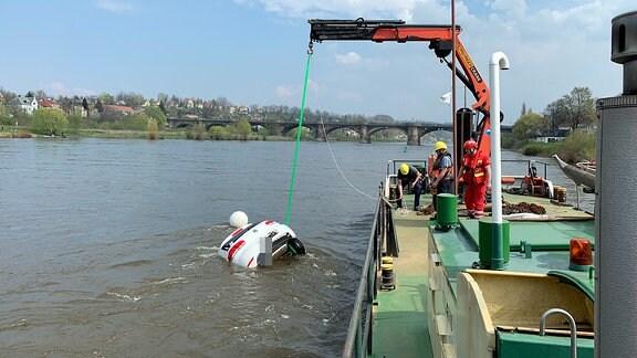 Ein Auto wird an einem Kran aus der Elbe auf ein Schiff gezogen
