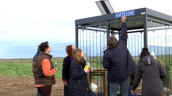 """Ein Mann mit einer dunkelblauen Jacke hält ein grellblaues Schild an ein gläsernes Wartehäuschen. Auf dem Schild steht """"Wartezone"""". Drumherum stehen Erwachsenen mit Winterklediung und Sektgläsern in der Hand. Sie schauen auf das angehaltene Schild"""