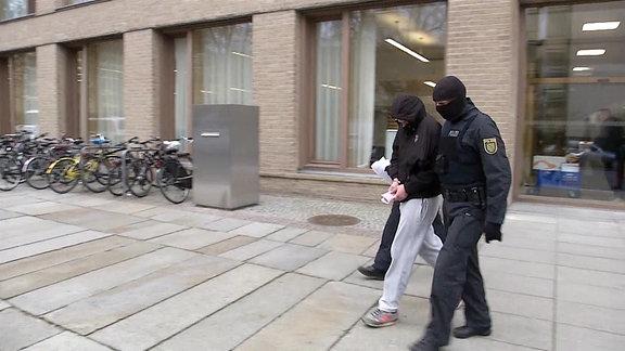 Zwei maskierte Polizisten bringen einen Festgenommenen aus dem Amtsgericht Dresden.