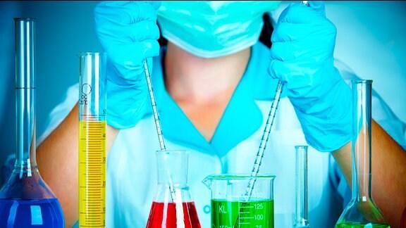 Verscheidene Laborgeräte und Behälter mit bunten Flüssigkeiten