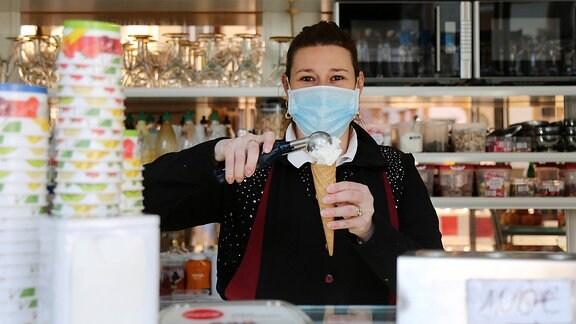 Eine Eisverkäuferin mit Mundschutz