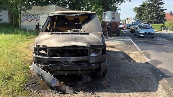 Ein Transporter steht ausgebrannt am Straßenrand