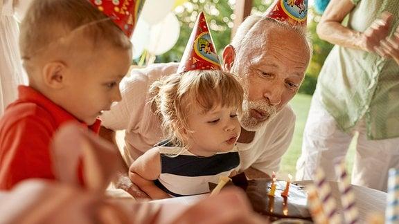 Ein Mann und zwei Kleinkinder an einem Geburtstagstisch