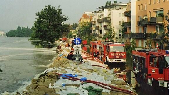 Feuerwehrautos stehen am Elbufer in Pieschen hinter einem Damm aus Sandsäcken.