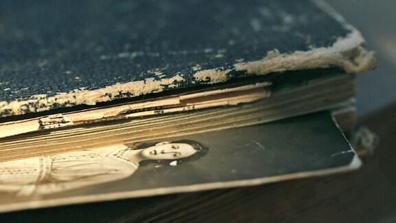 Das Foto einer Frau steckt zwischen den Seiten eines alten Buches