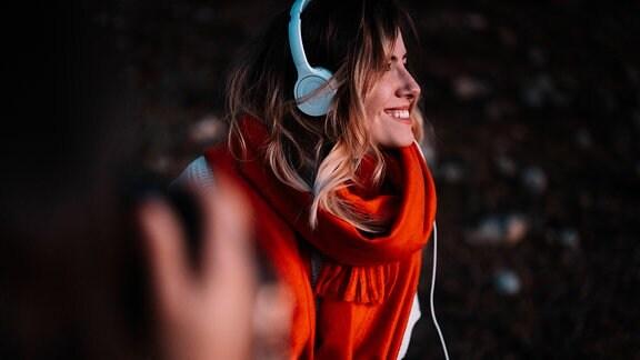 Frau hört lächelnd Musik über Kopfhörer