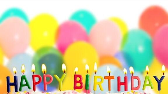 """Bunte Buchstabenkerzen bilden den Schriftzug """"Happy Birthday"""" auf einem Geburtstagskuchen."""