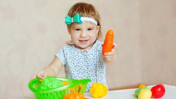 Kleinkind hält Plastemohrübe