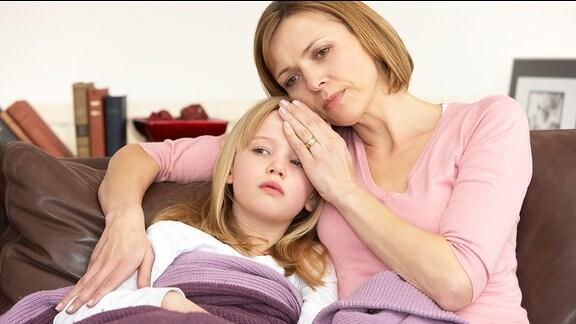 Mutter sitzt mit krankem Kind auf der Couch.