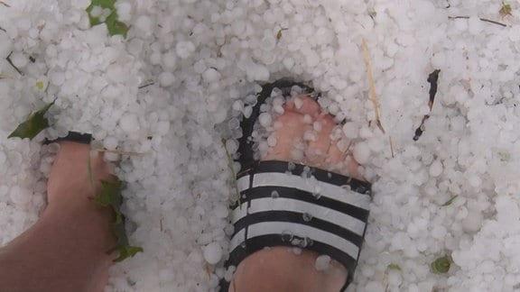 Füße in Badeschlappen stehen in einem Berg Hagelkörner in Auerswalde.