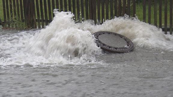 Wassermassen drücken einen Gullydeckel hoch.
