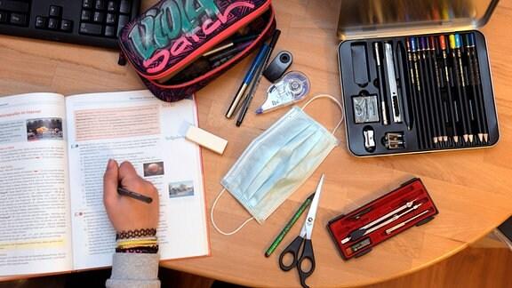 Ein Kind arbeitet an einem Schreibtisch, auf dem Schulmaterialien und eine Corona-Maske liegen.