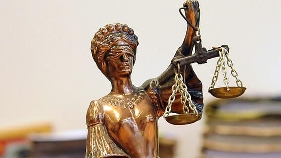 Eine goldfarbene Justitia-Figur steht im Landesarbeitsgericht Berlin-Brandenburg vor Aktenbergen.