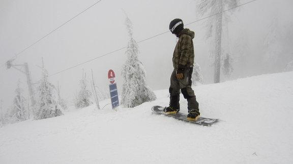 Ein Snowboarder steht 2012 an einer Abfahrt.