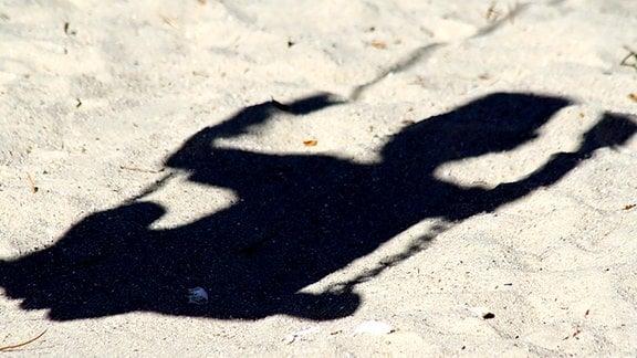 Schatten eines Kindes auf einer Schaukel.