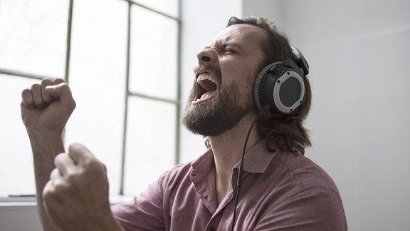 Ein Mann mit Kopfhörern singt.