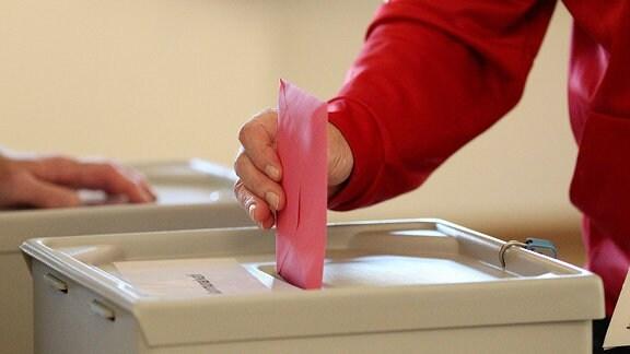 Mensch steckt Stimmzettel in eine Wahlurne.