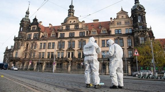 Zwei Mitarbeiter der Spurensicherung stehen vor dem Residenzschloss mit dem Grünen Gewölbe.