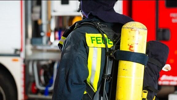 Feuerwehrmann von hinten mit Sauerstoffflasche auf dem Rücken