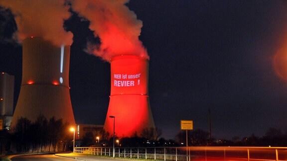 """Ein Turm des Kraftwerks Lippendorf wird mit rotem Licht angestrahlt. Darauf steht """"Hier ist unser Revier"""""""