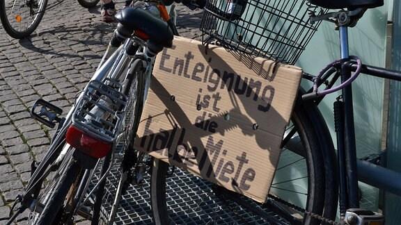 """Pappschild """"Enteignung ist die halbe Miete"""" an einem Fahrrad befestigt."""