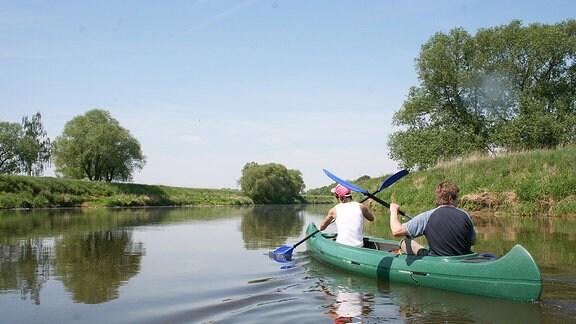 Zwei Personen fahren in einem Kanu auf einem Fluss.