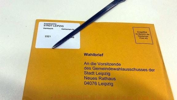 Ein Briefwahlumschlag für die Leipziger Oberbürgermeisterwahl liegt auf einem Tisch