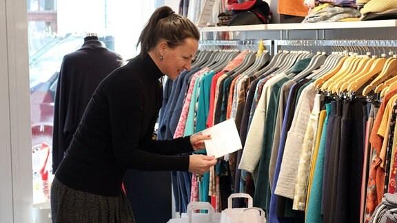 Frau in einem Einzelhandelsgeschäft liest lächelnd Zeilen auf einer Karte. Vor ihr stehen mehrere weiße Papiertüten mit Inhalt.