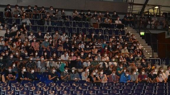 Menschen mit Mund-Nase-Schutz sitzen in der Arena Leipzig.