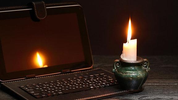 Eine brennende Kerze neben einem ausgeschaltetem Laptop in einem dunklen Raum.