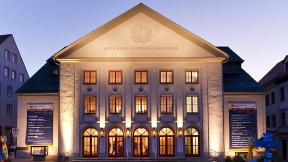 Theaterhaus in Freiberg in der abendlichen Dämmerung, über dem Eingang an der Fasade ist der Schriftzug 'Die Kunst gehört dem Volke' zu lesen.