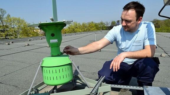 in Mann im hellblauen T-Shirt hockt vor einem grünen Gerät