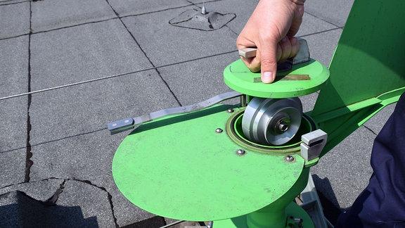 eine Hand an einem grünen Gerät