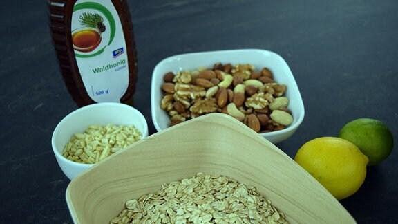 Zutaten für ein Müsli, wie Nüsse, Haferflocken und Honig  Auch ein Müsli ist schnell selbst gemacht und gesünder als Fertigmüsli …