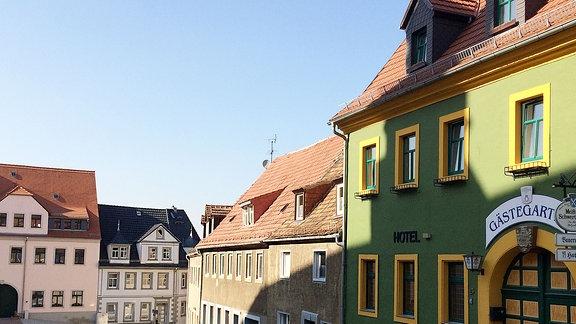 Eine bergab führende Straße mit einem Gasthaus und Wohnhäusern, liegt unter blauem Himmel.