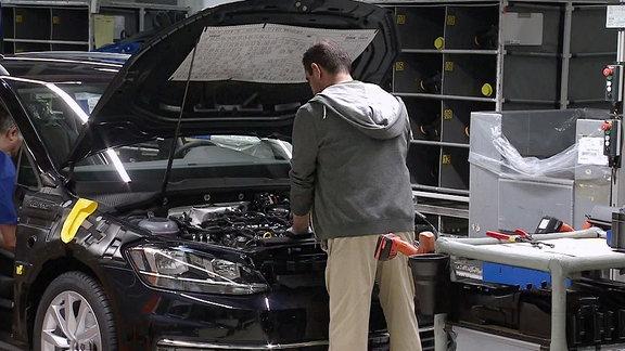 Ein Automonteur steht vor einem PKW mit geöffneter Motorhaube und schaut in den Motor.