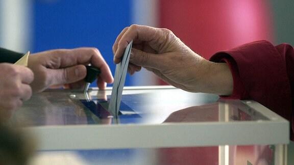 Wahlzettel wird in eine Wahlurne geworfen